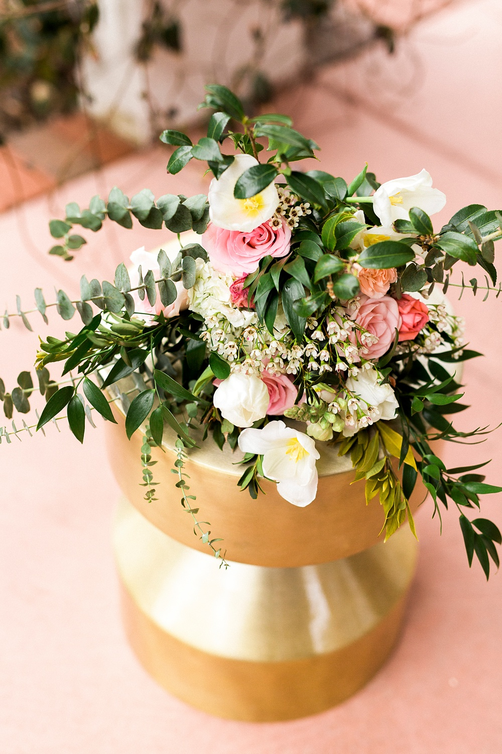 bouquet rests on a gold stool