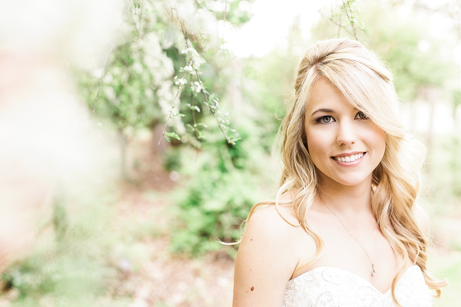 Bride smiling in white spring blooms