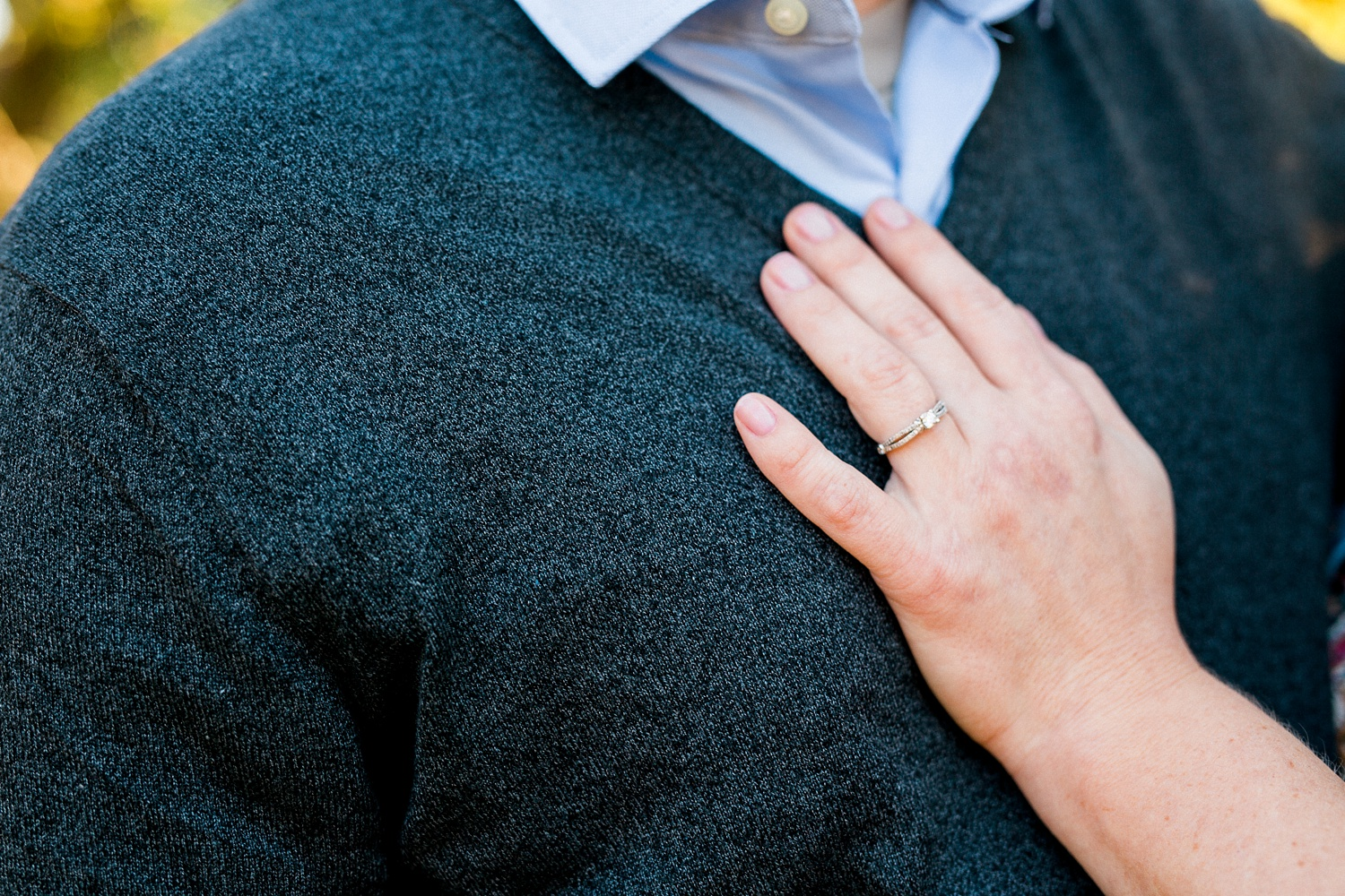 woman rest her hand on her fiance's chest