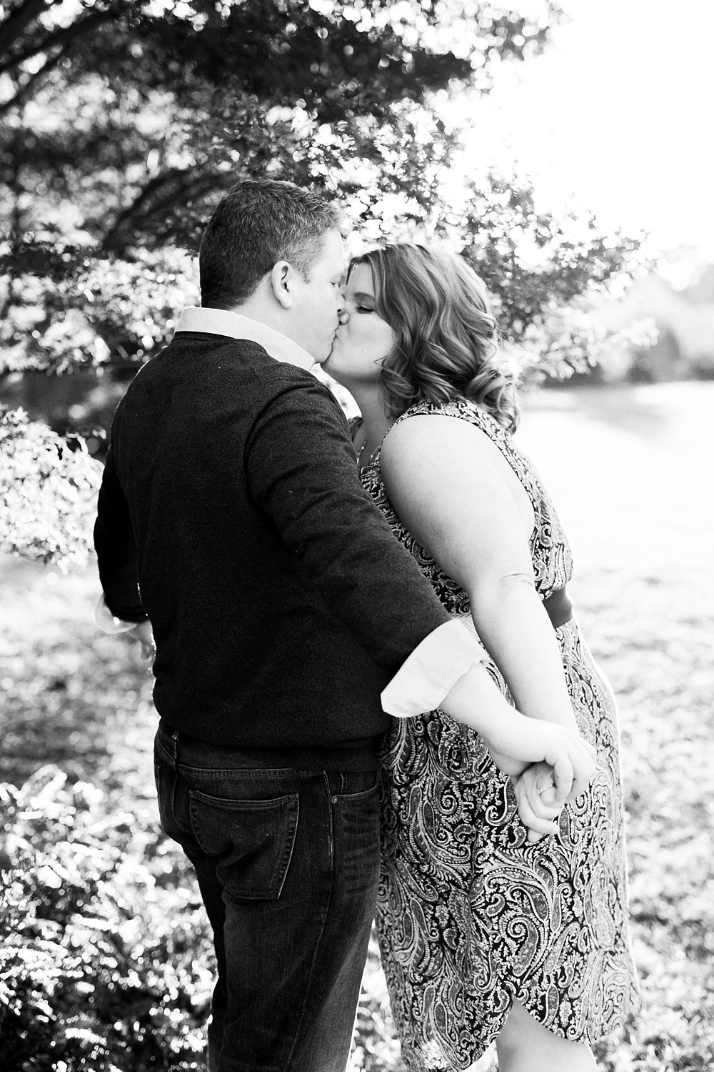 Couple kisses under a tree at NC State's JC Raulston Arboretum