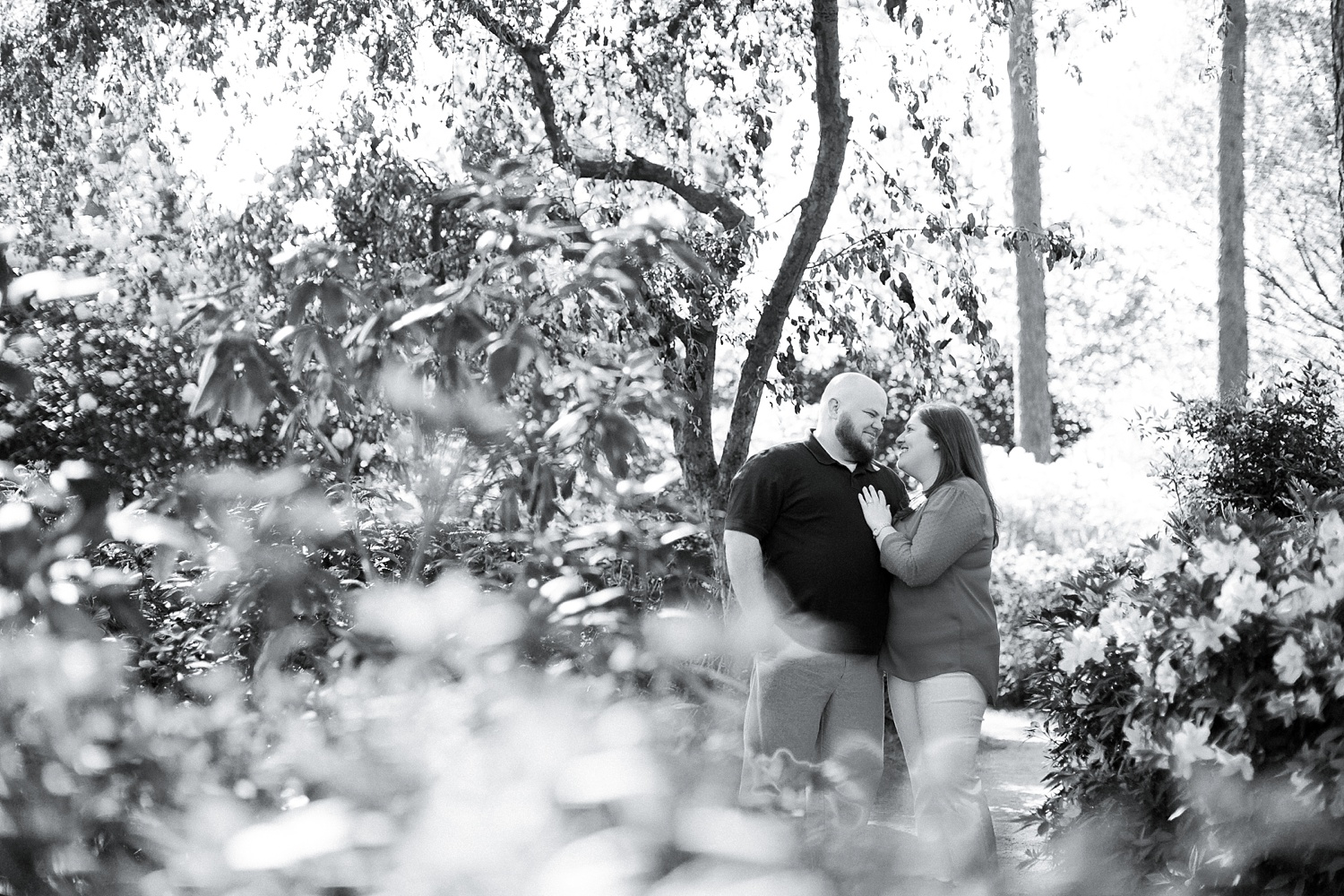 couple snuggles in the gardens at their engagement session