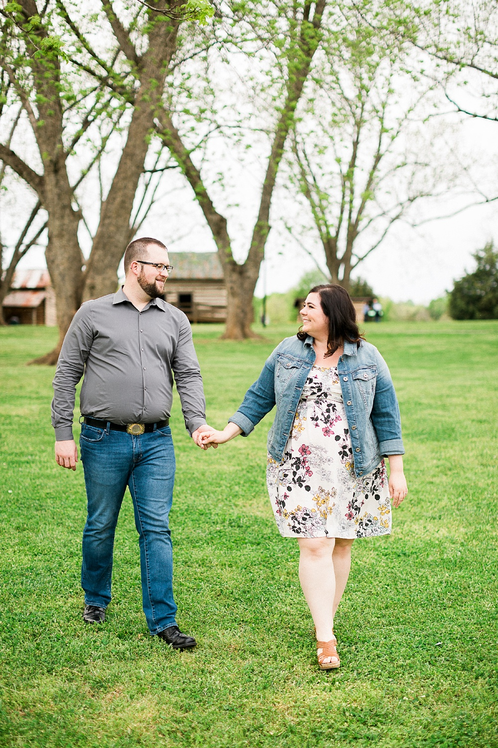 engaged couple holds hands and walks