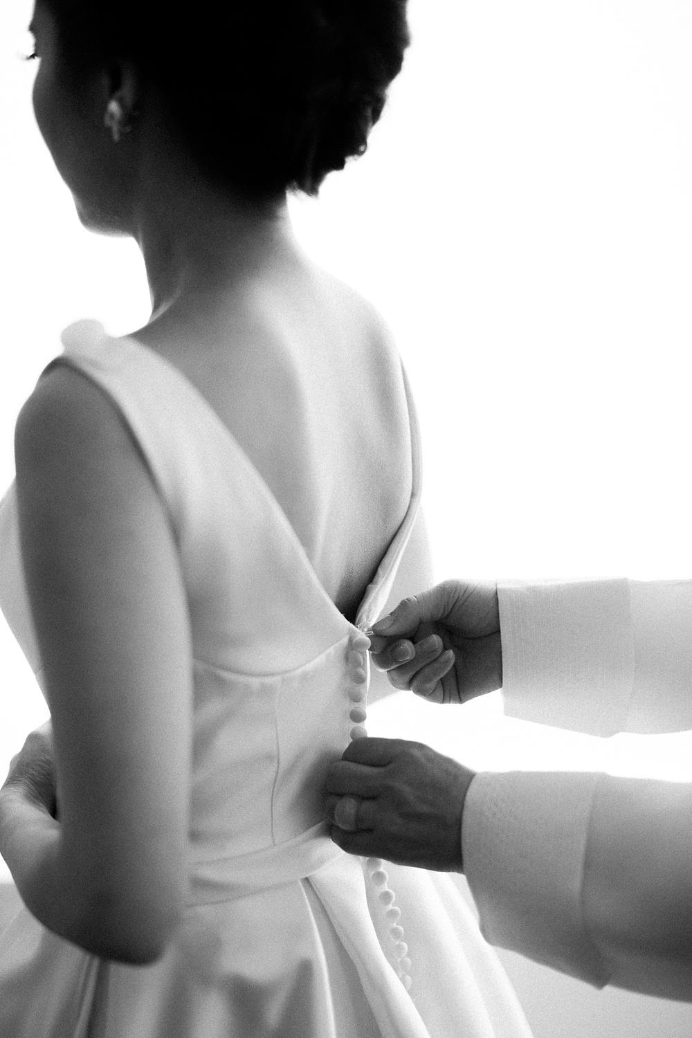 bride being zipped into her wedding dress