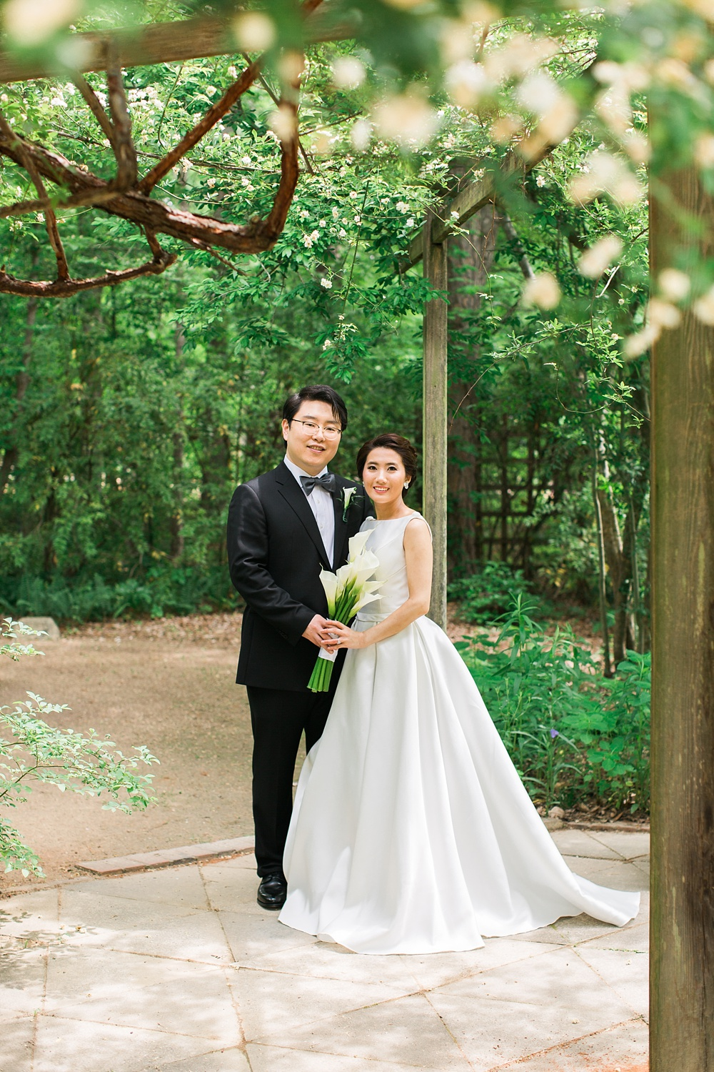 Bride + Groom under an arbor at the UNC botanical garden in Chapel Hill, NC