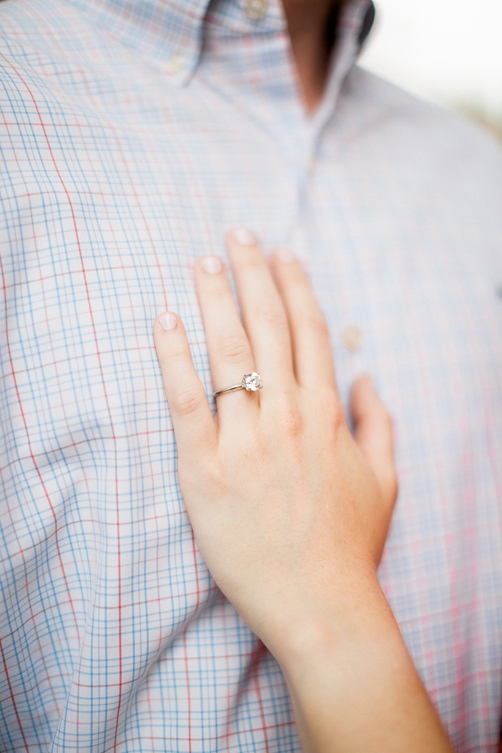 woman's hand with her classic solitaire engagement ring