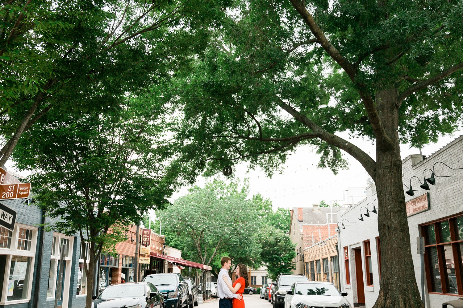 couple embraces under the trees at Raleigh's City Market