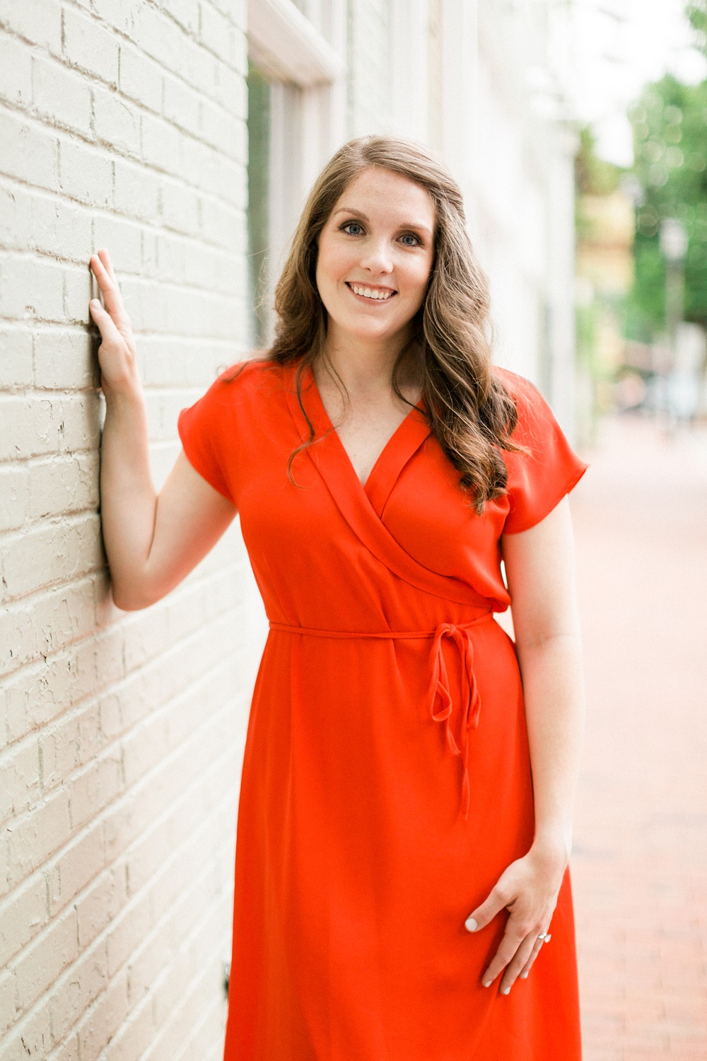 woman smiles and leans against a brick wall