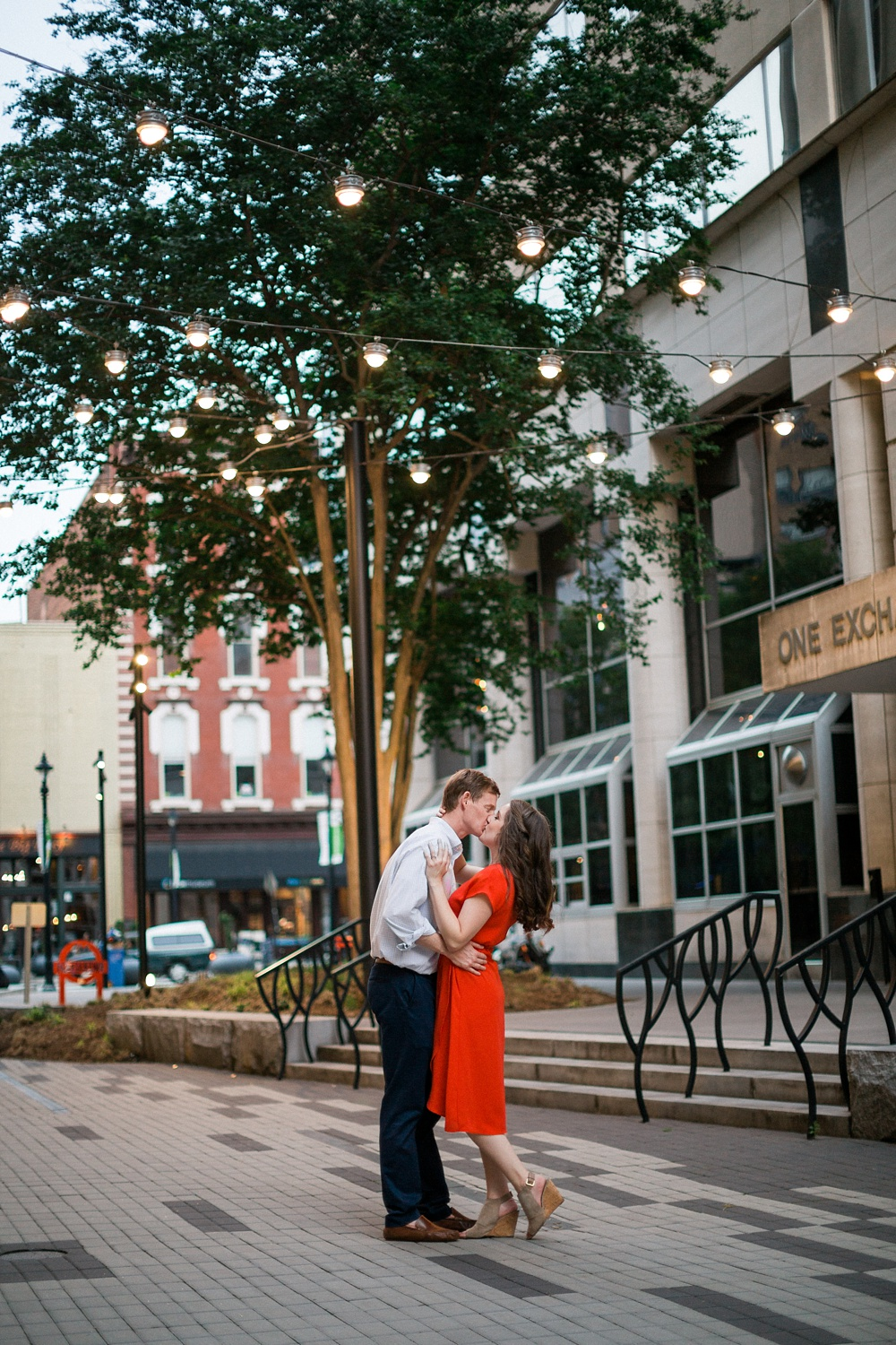 couple kisses under the market lights in downtown raleigh