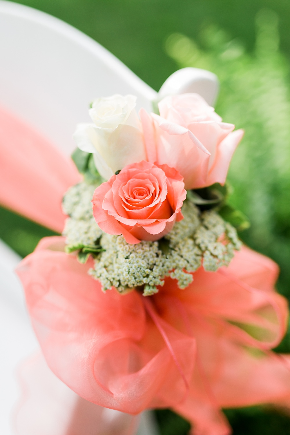 closeup of rose bundle tied to a white wedding chair