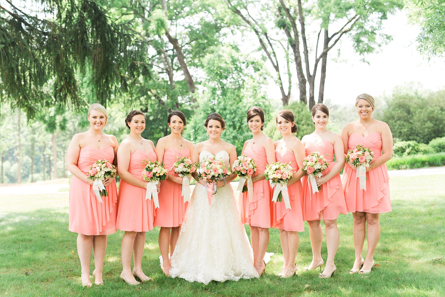 bridal party stands on a green lawn for their group portrait