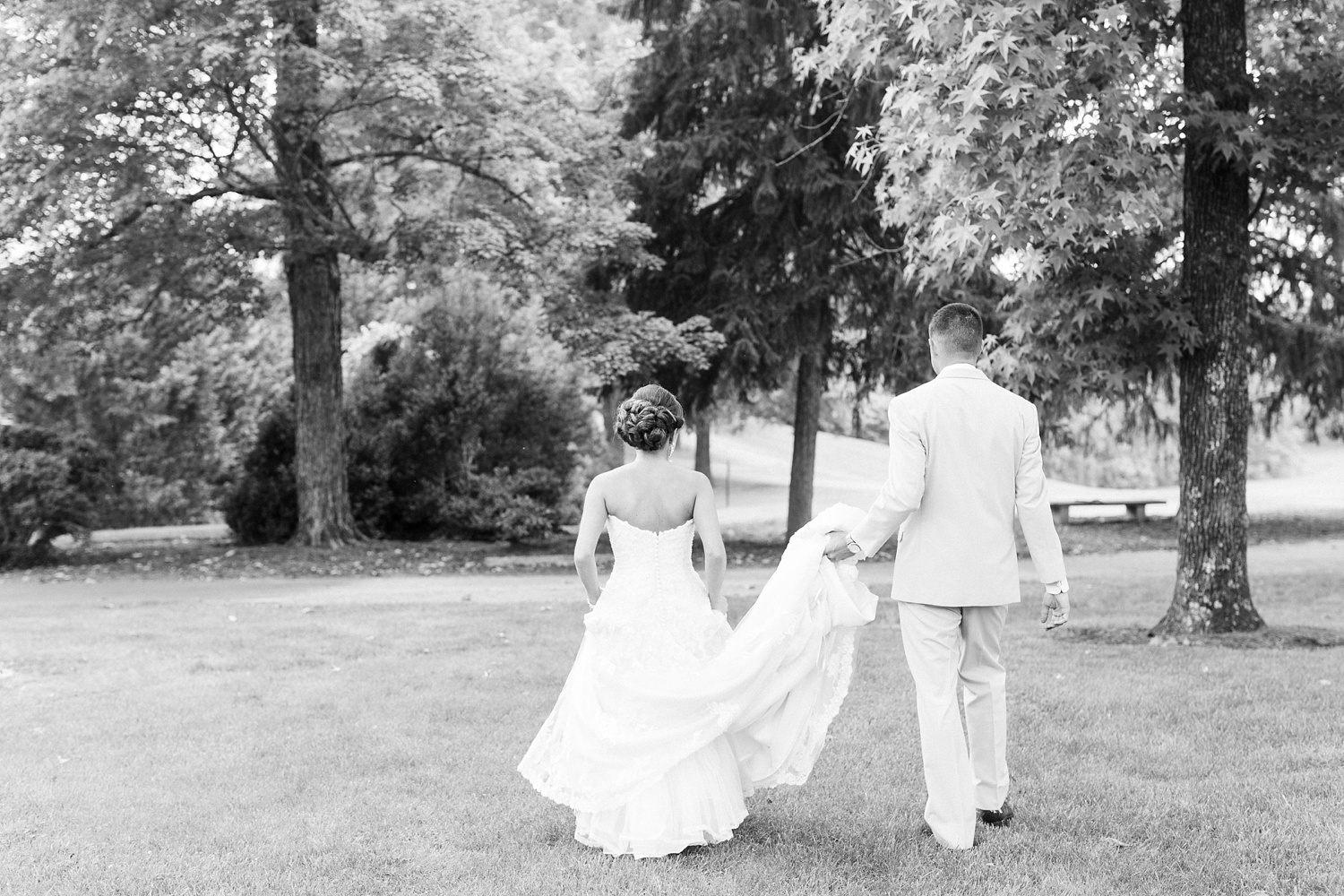 groom holds his wife's dress as they walk through the woods