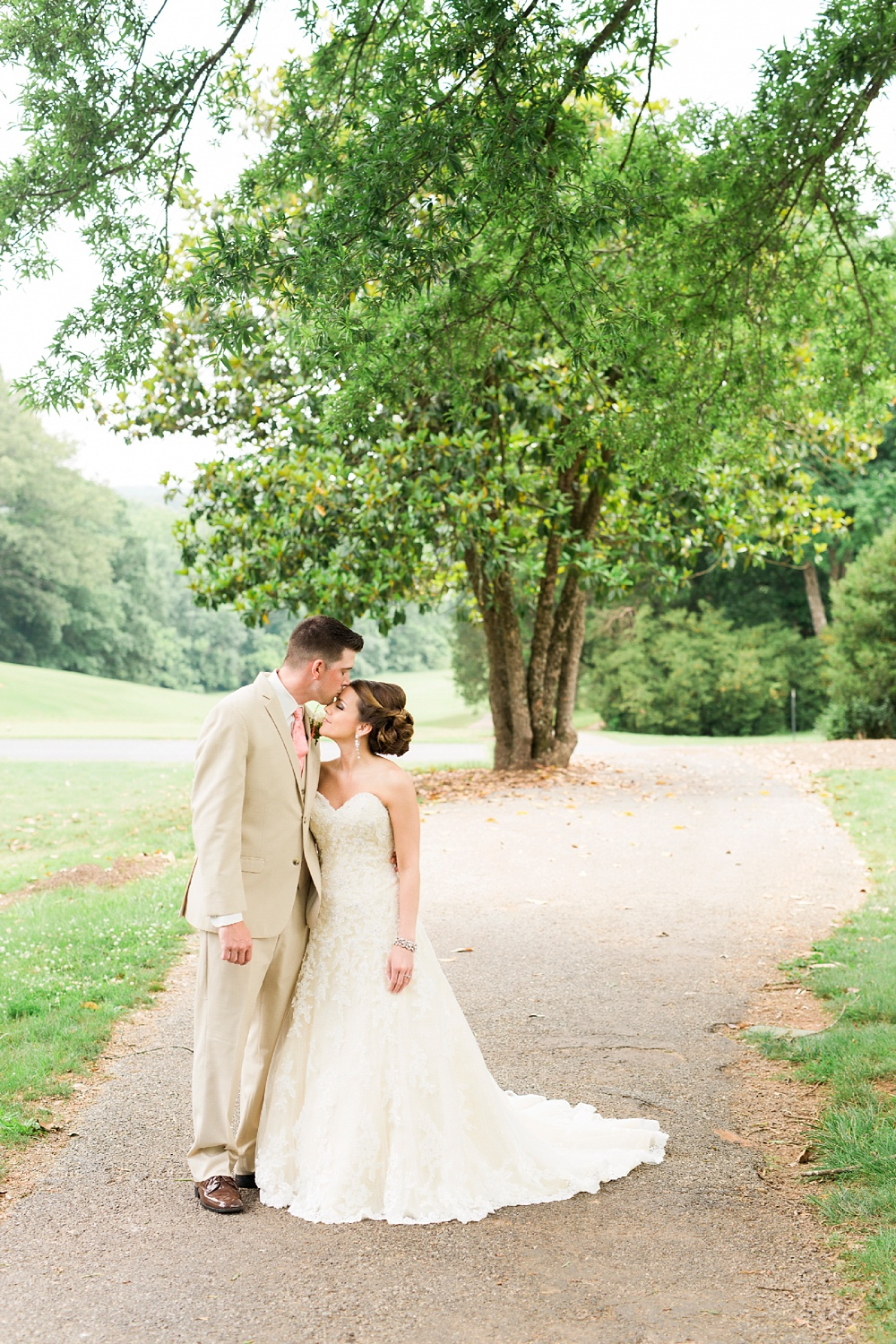 bride and groom hold each in front of the first hole greenway