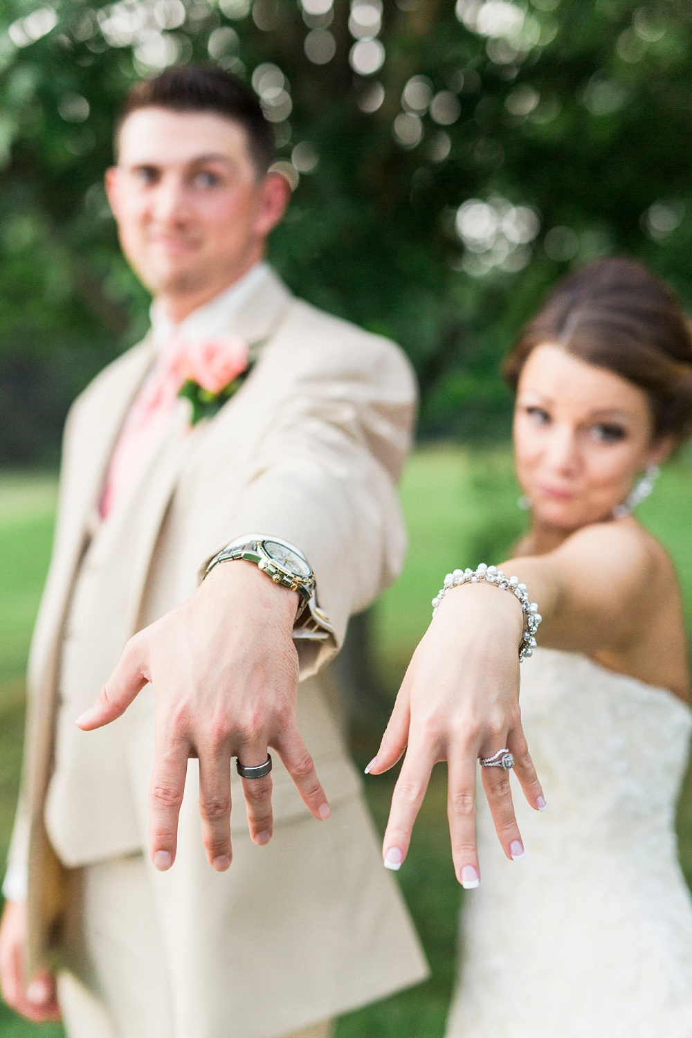 bride and groom show off their new wedding rings