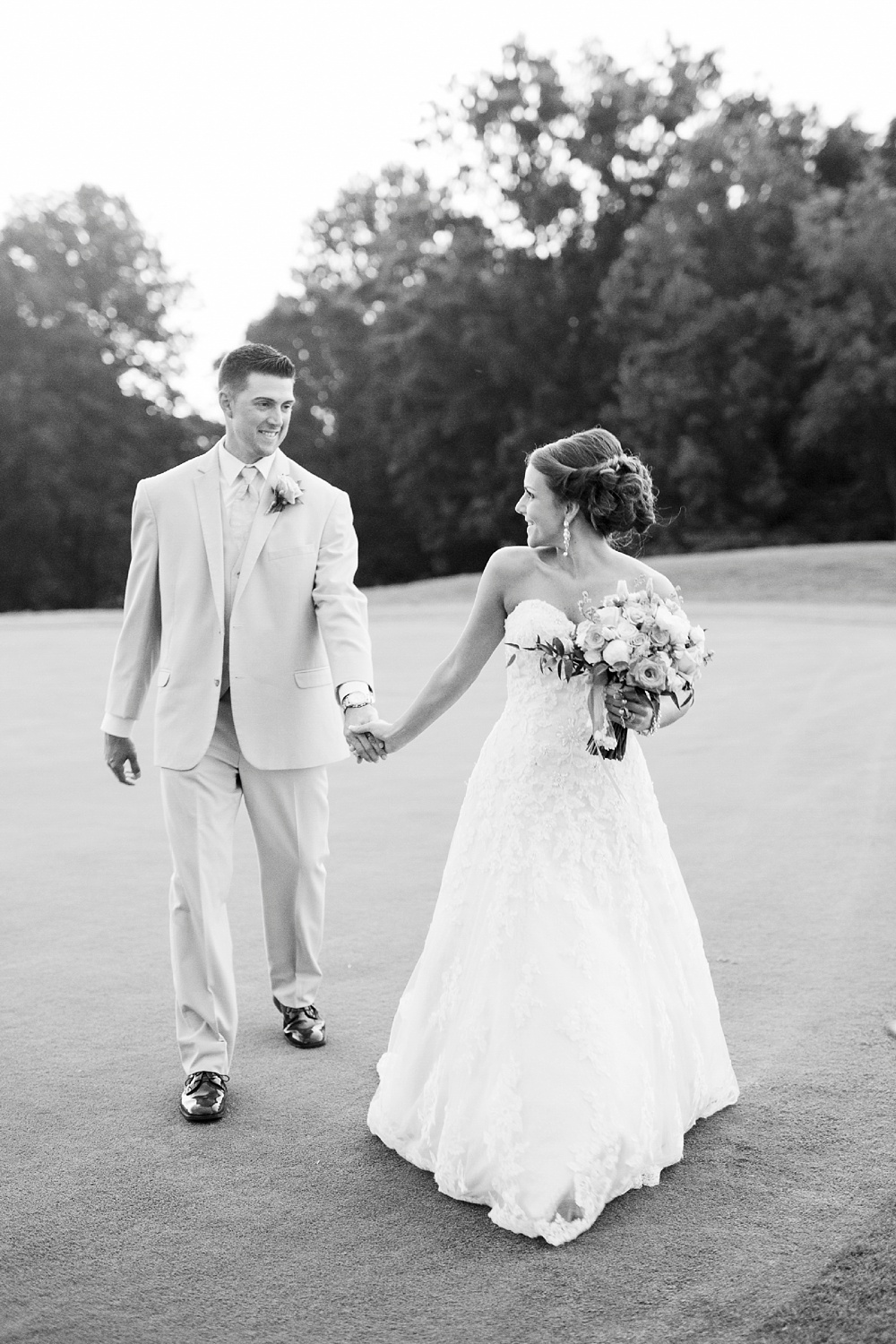 bride and groom walk hand in hand across the putting green