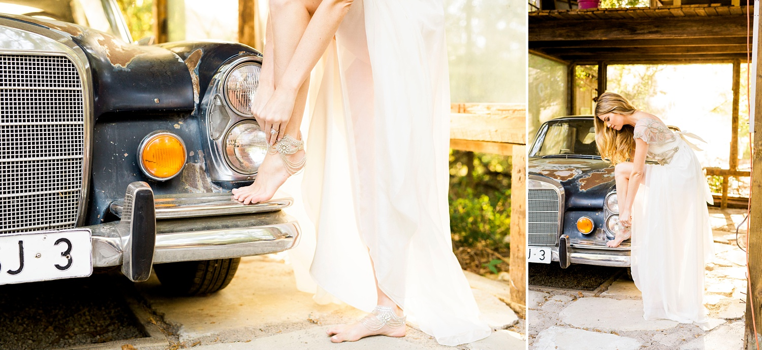 bride adjusts her foot jewelry on the bumper of an old car