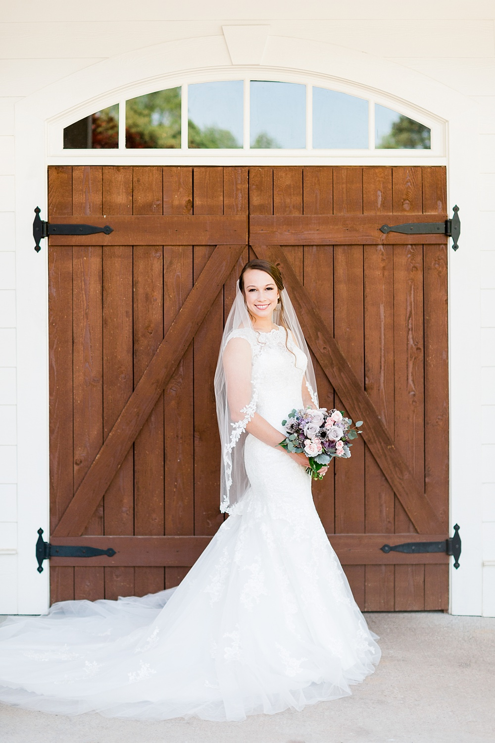 bride poses in front of barn doors for a portrait