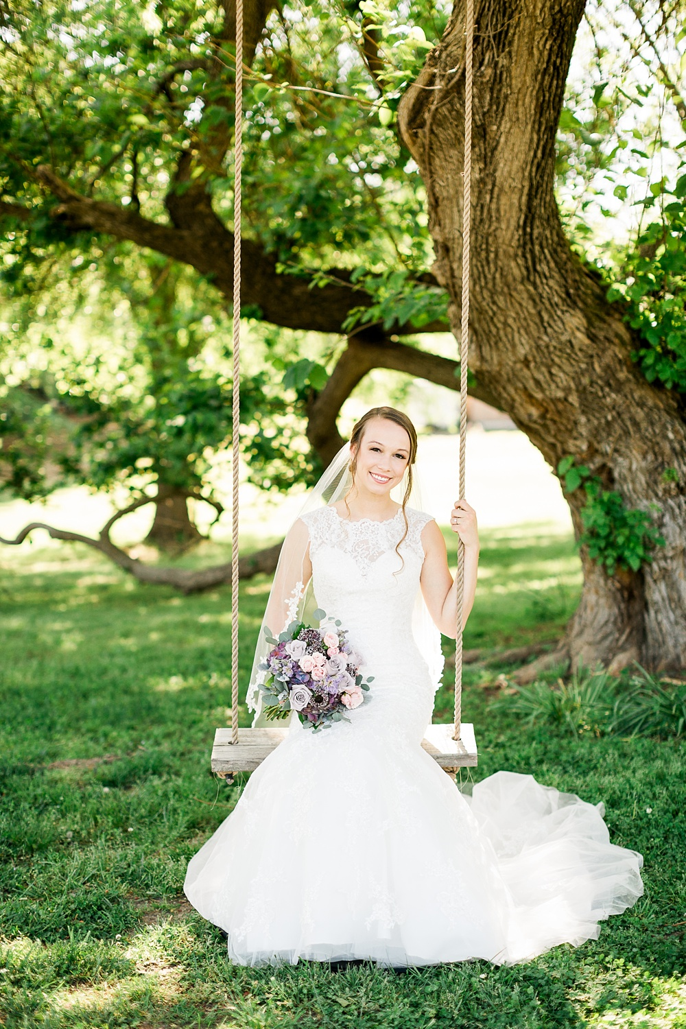bride sits on a rope swing under an old oak tree