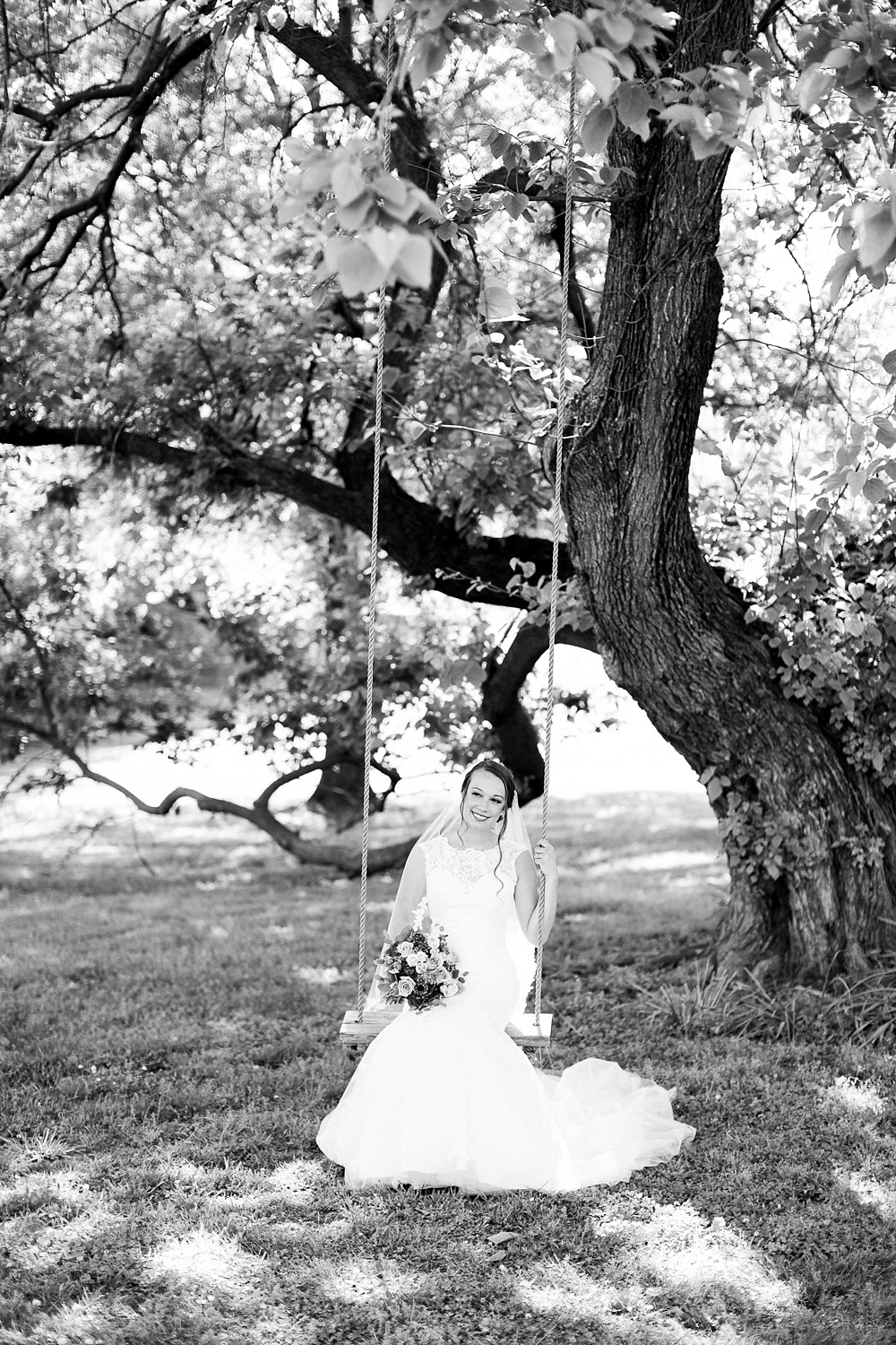 bridal portrait of a bride sitting on an old swing hung from an oak tree