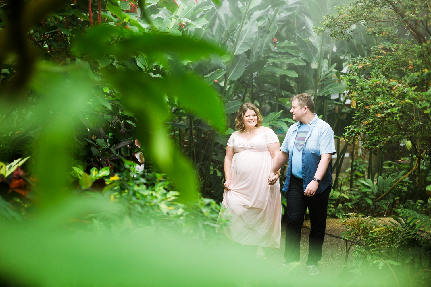 expecting couple walks through a greenery filled butterfly house