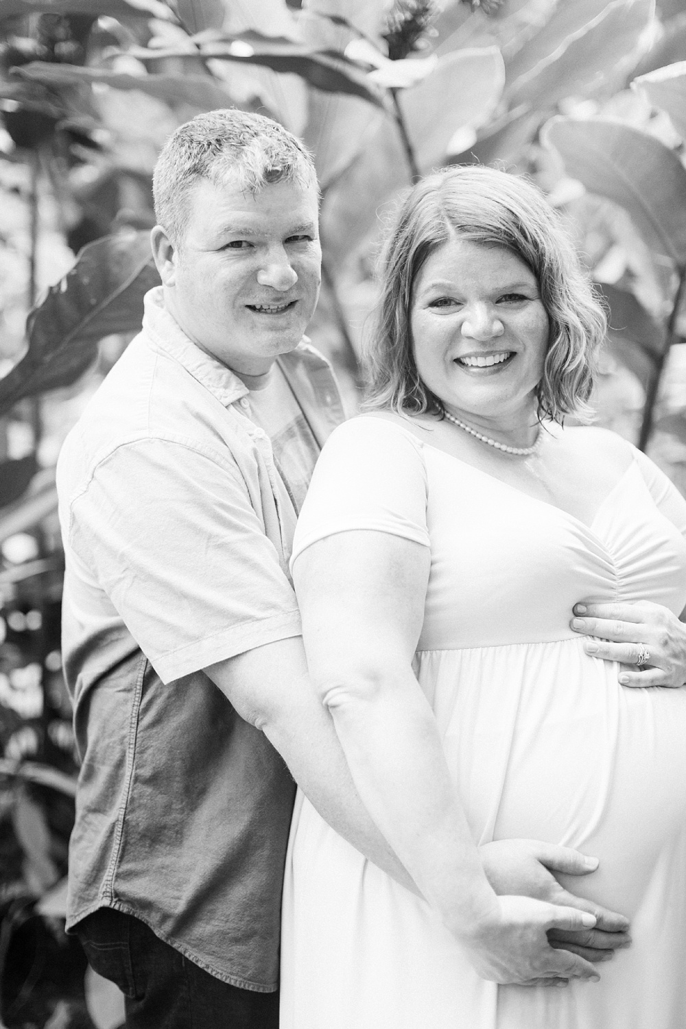 husband and wife cradle wife's pregnant belly