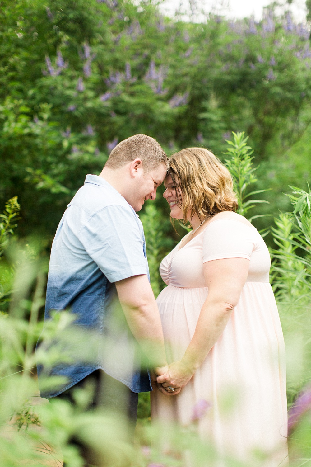 husband and wife touch foreheads in a garden