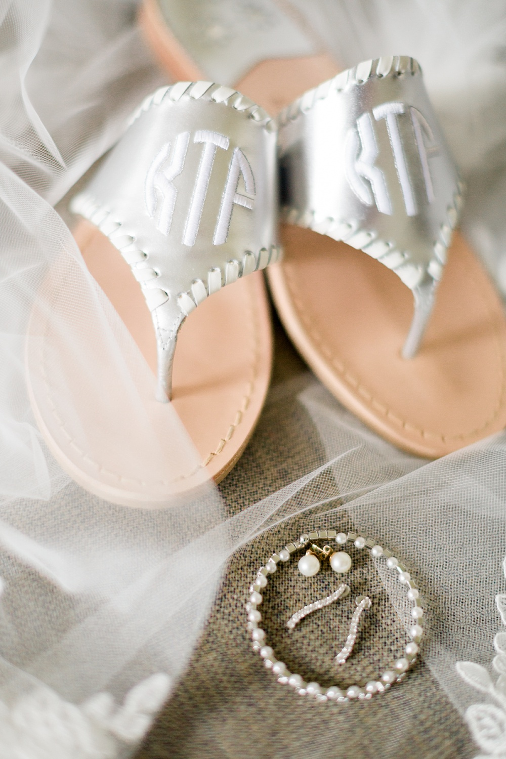 bride's monogrammed jack rogers sandals lay on a veil with her wedding jewelry