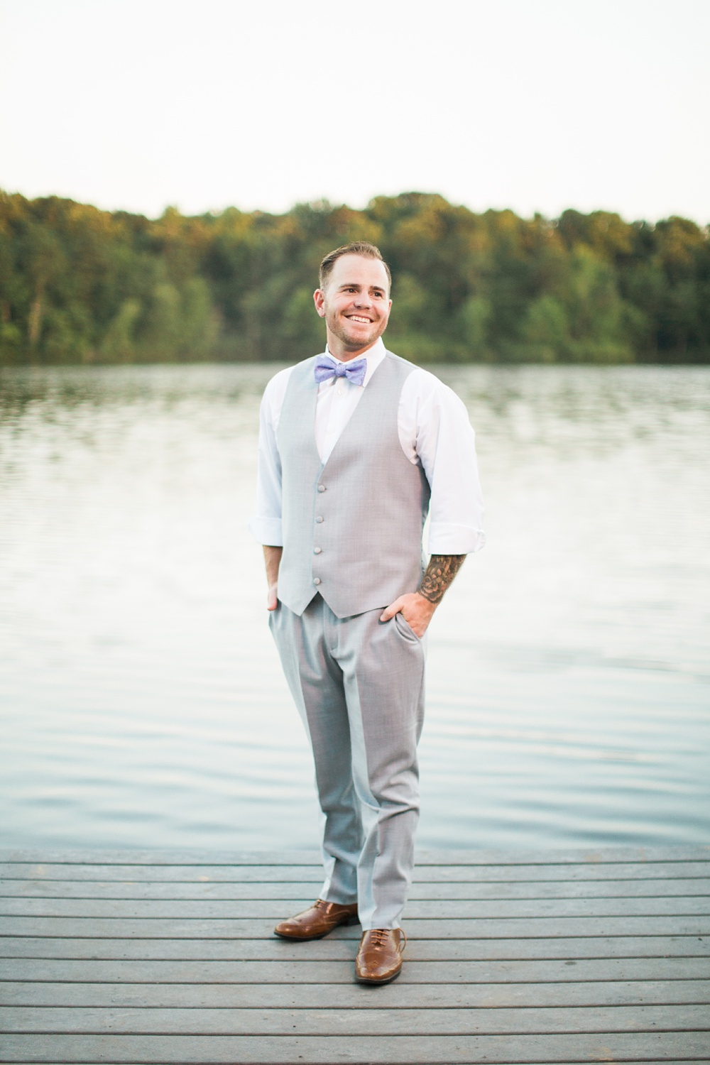 groom stands on a dock at a lake