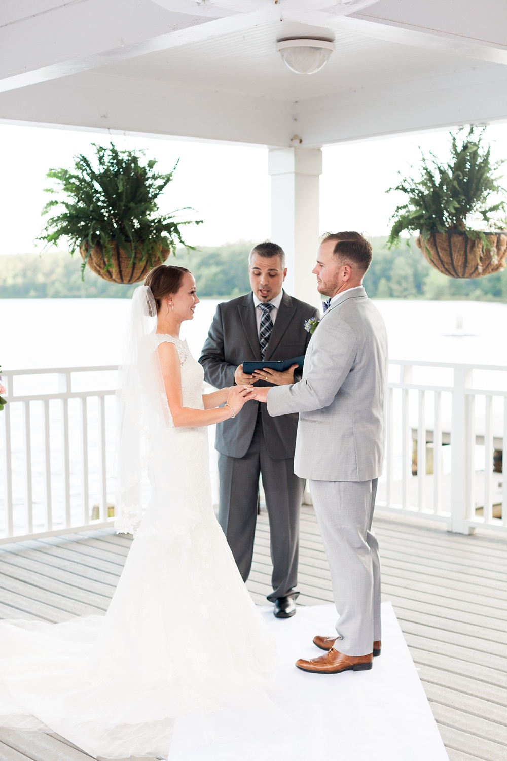 bride places the wedding band on her groom during their wedding ceremony