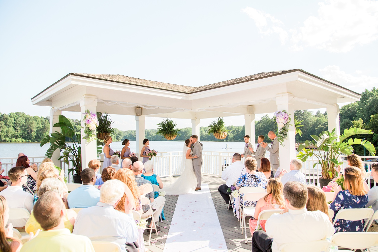 bride and groom share their first kiss at their lakefront wedding