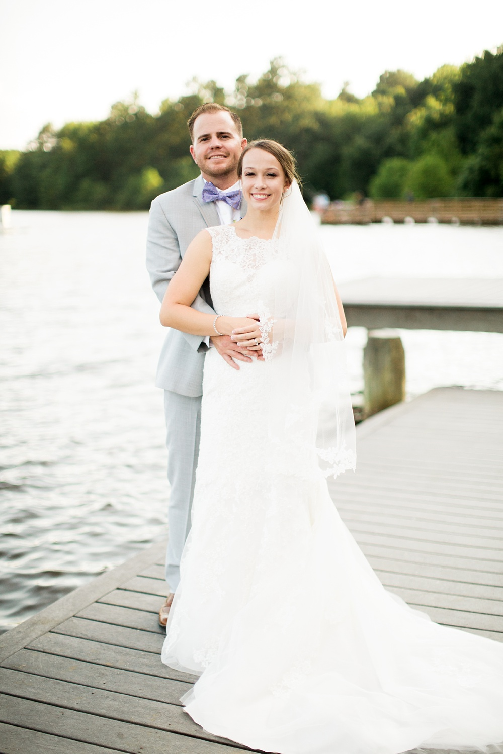 bride and groom on the docks at bass lake in holly springs, nc