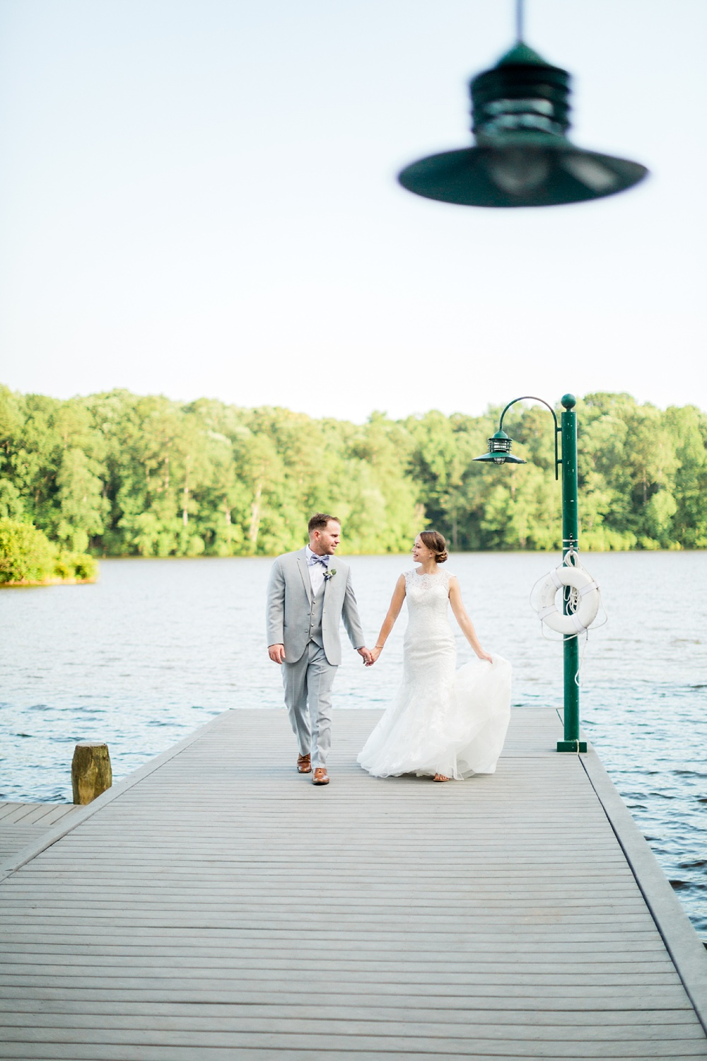 bride and groom walk down the docks at bass lake in holly springs, nc