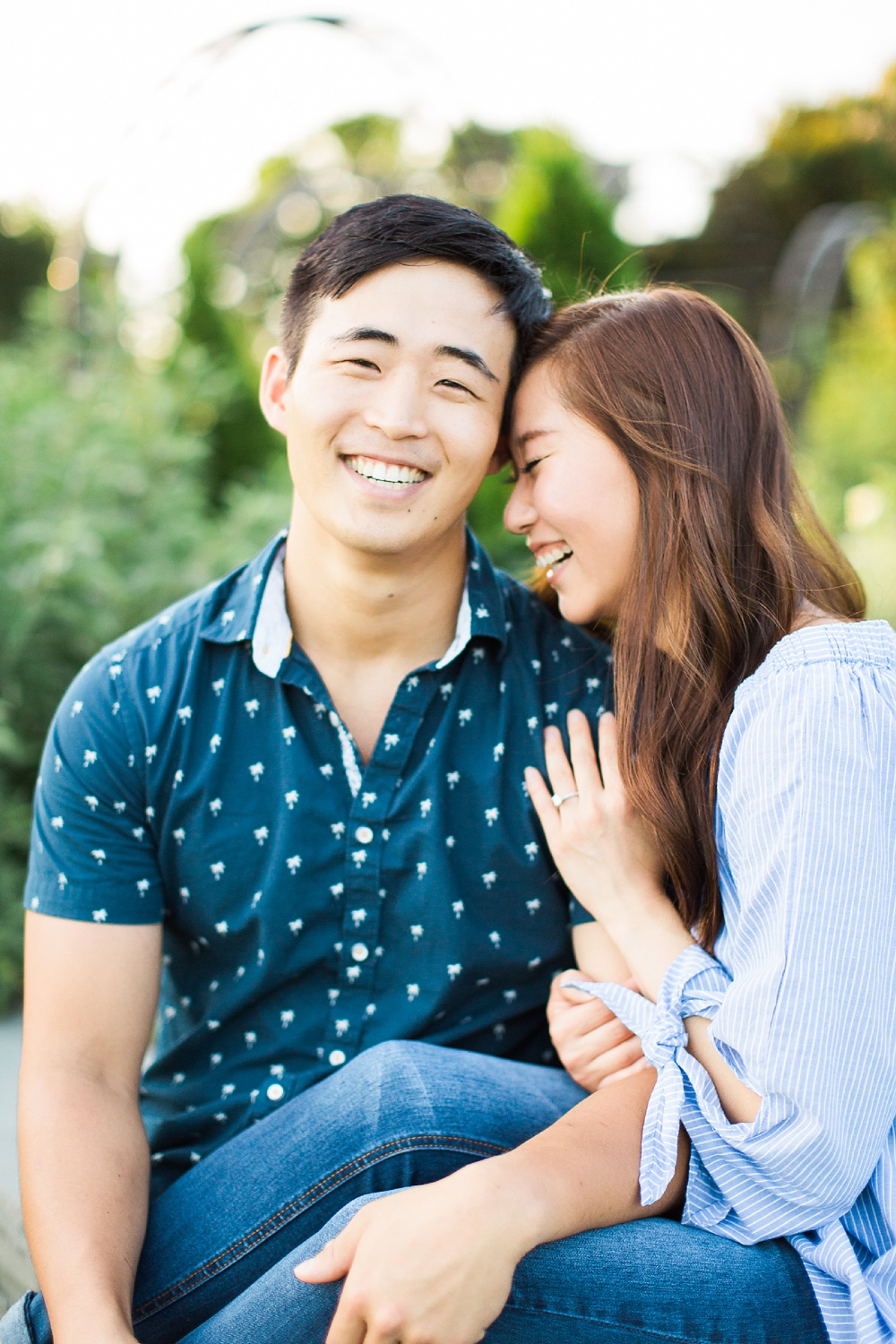 couple laughs and embraces while seated in a garden