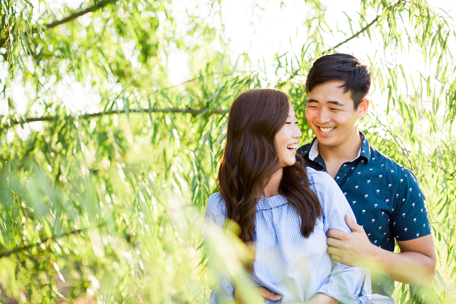 couples stands in a willow tree at golden hour