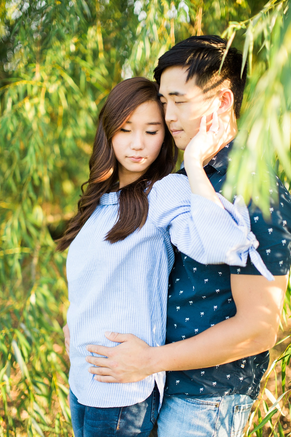 couple embraces under willow branches in the golden evening sun