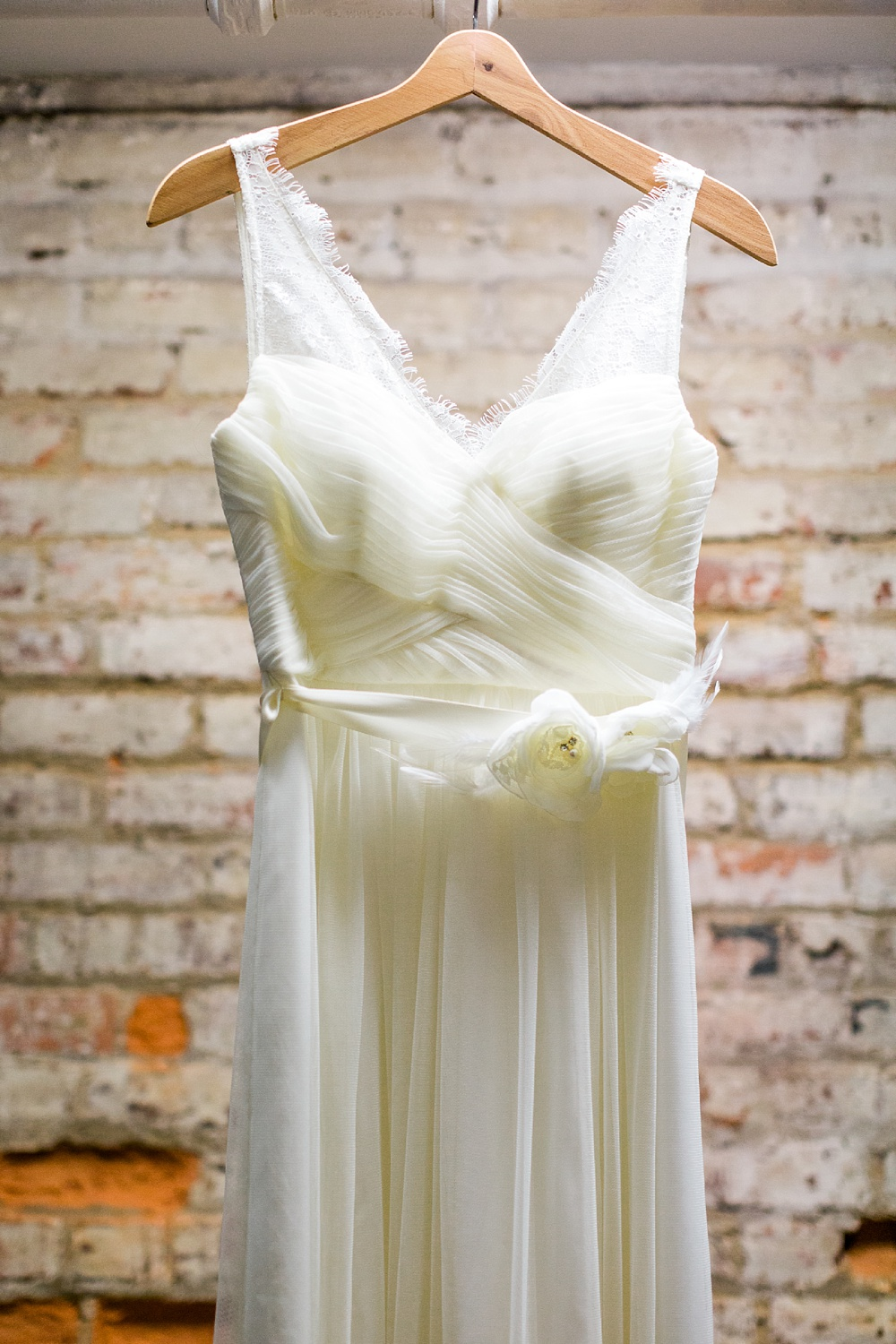 vintage wedding dress hangs in front of an exposed brick wall