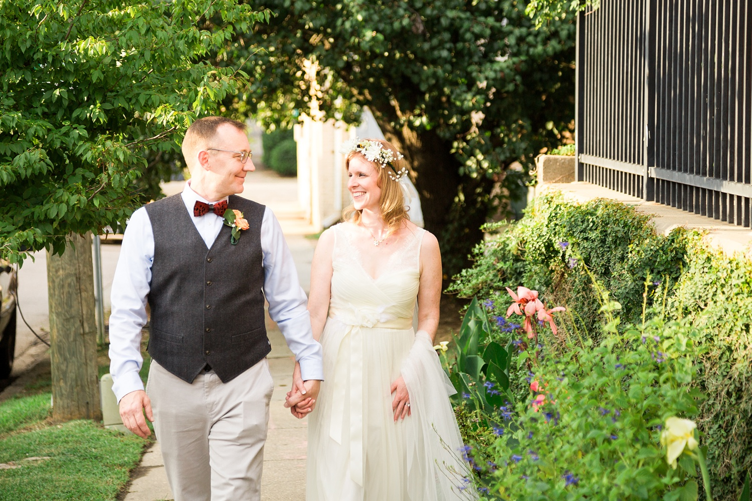 bride and groom walk down the sidewalk in downtown raleigh
