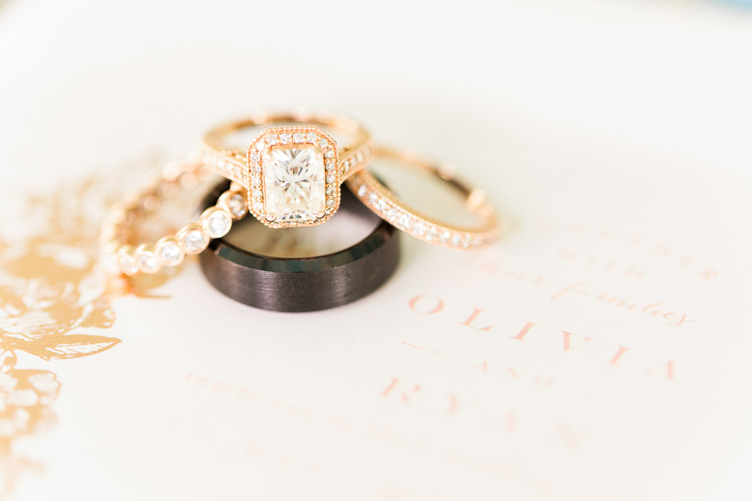 rose gold wedding rings on a wedding invitation