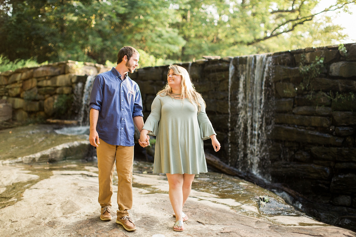 couple walks in front of a waterfall