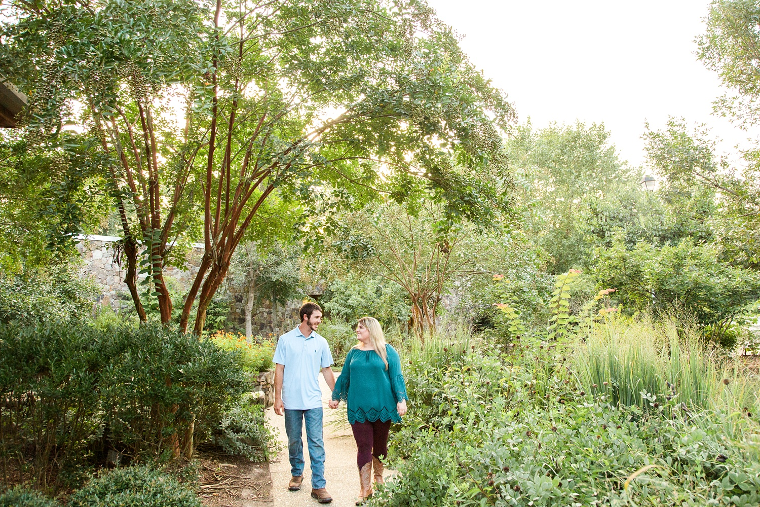 couple walks through the welcome center gardens at yates mill pond park