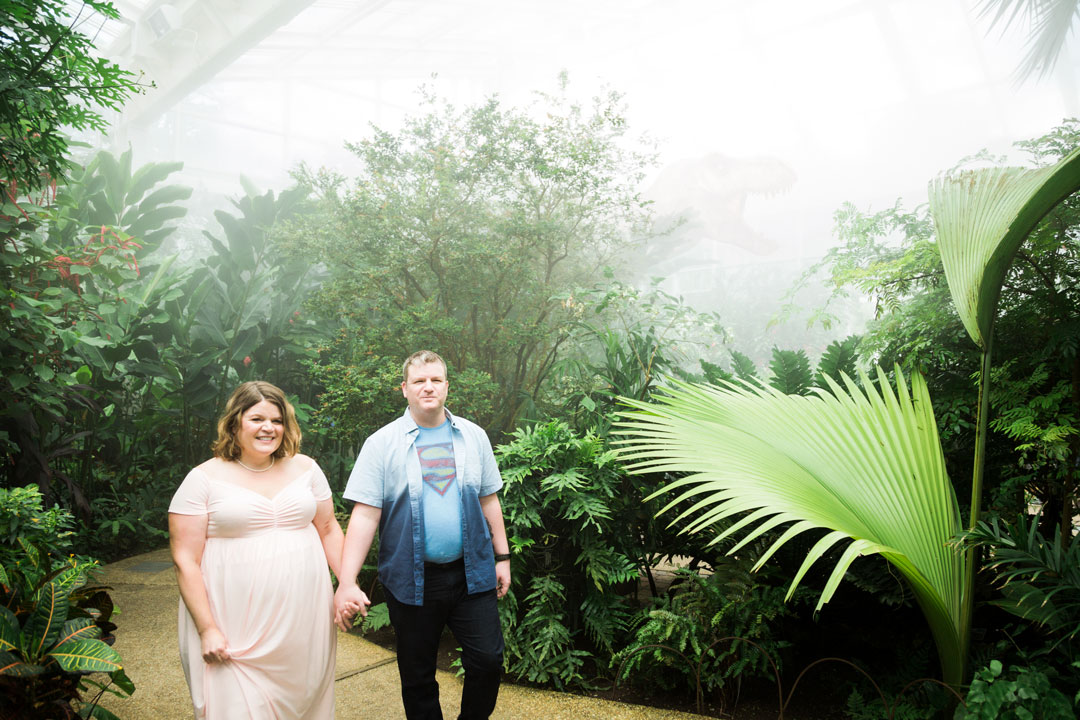 Man and pregnant woman walk in butterfly house with a dinosaur
