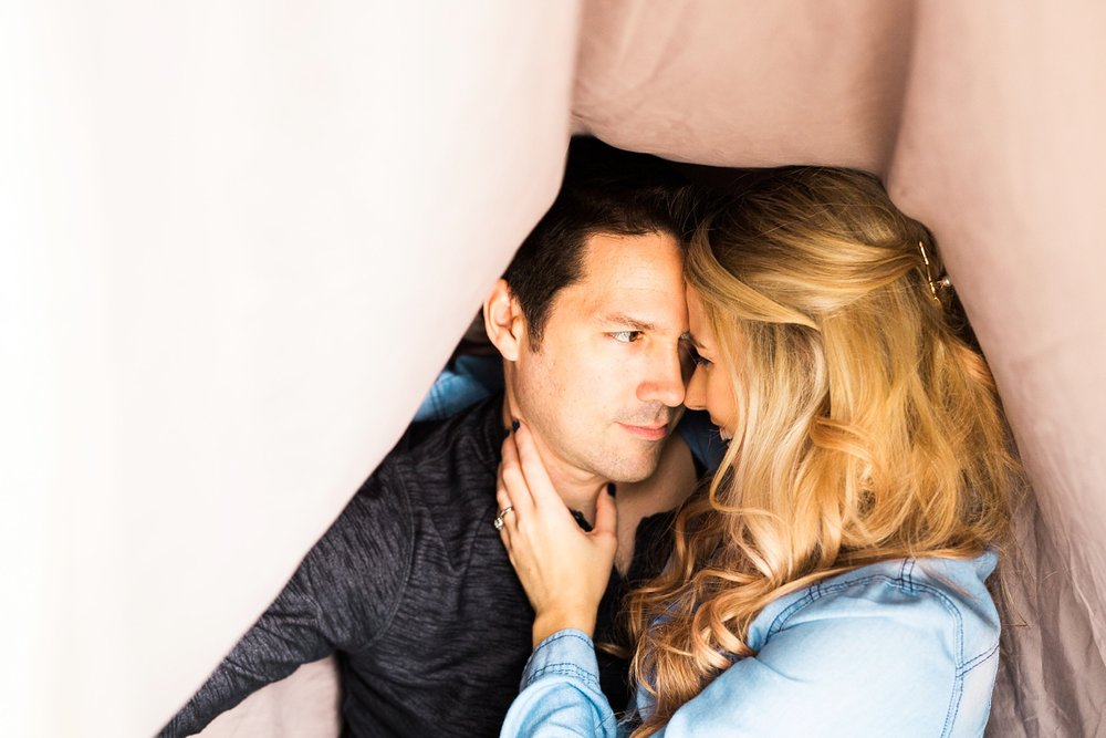 Newlyweds (Kristin + Ron) share a passionate moment under a blanket fort during their lifestyle session.