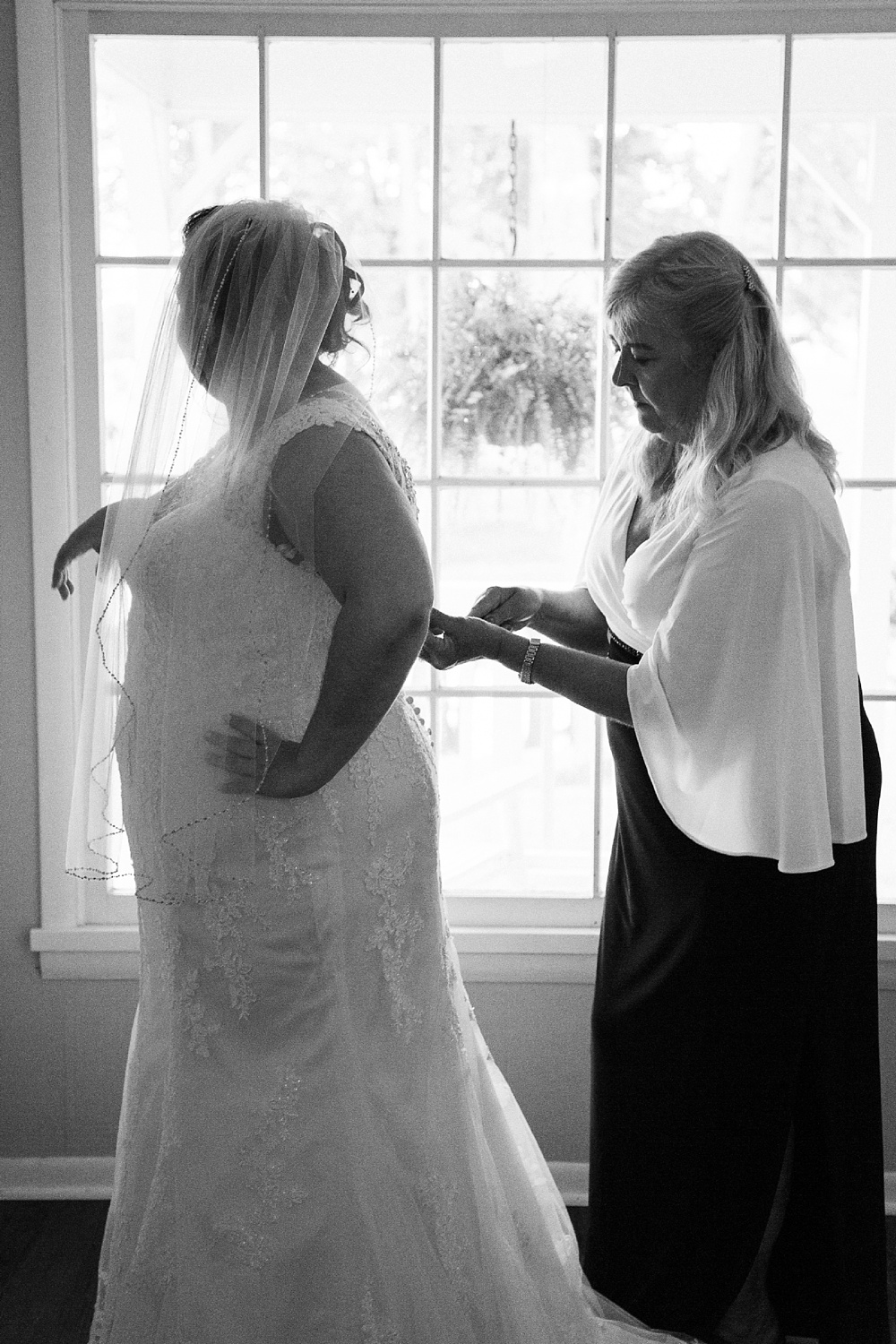 mother puts bride in her dress in front of a window