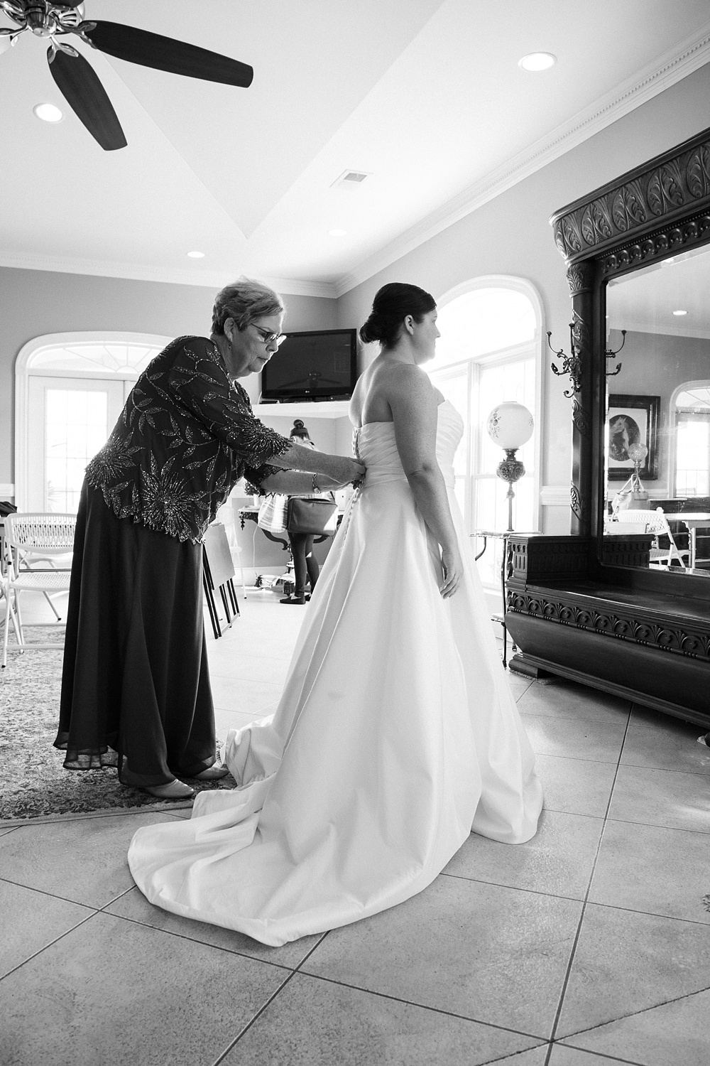 bride's mother helps her into her wedding gown