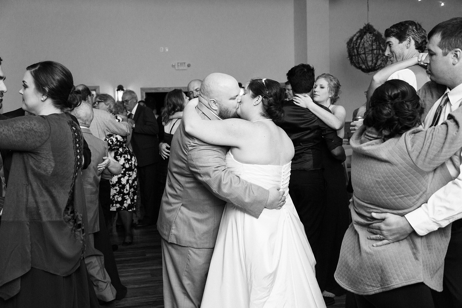 bride and groom kiss while dancing at their reception