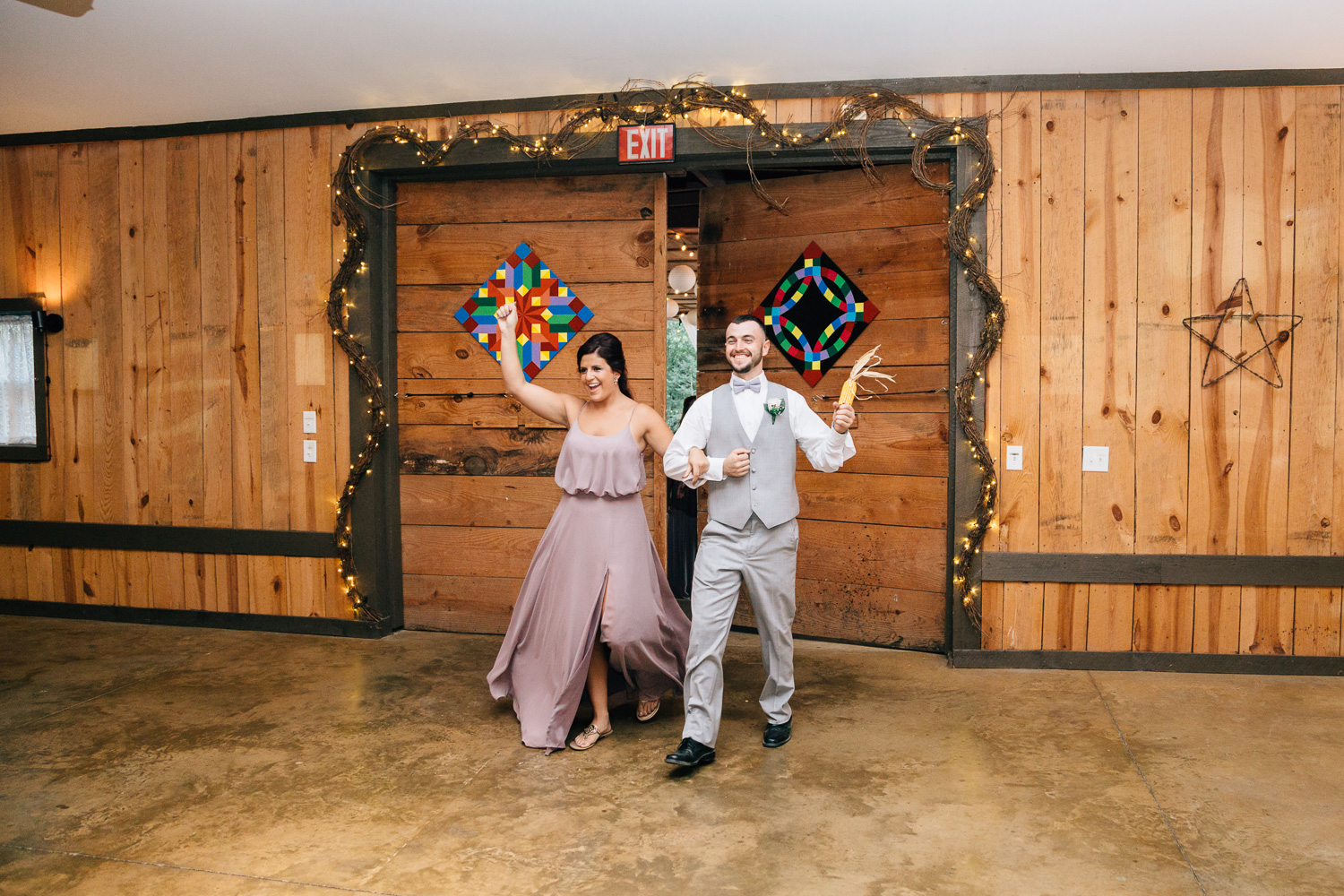 Bridesmaid and groomsman enter reception with natural wood background
