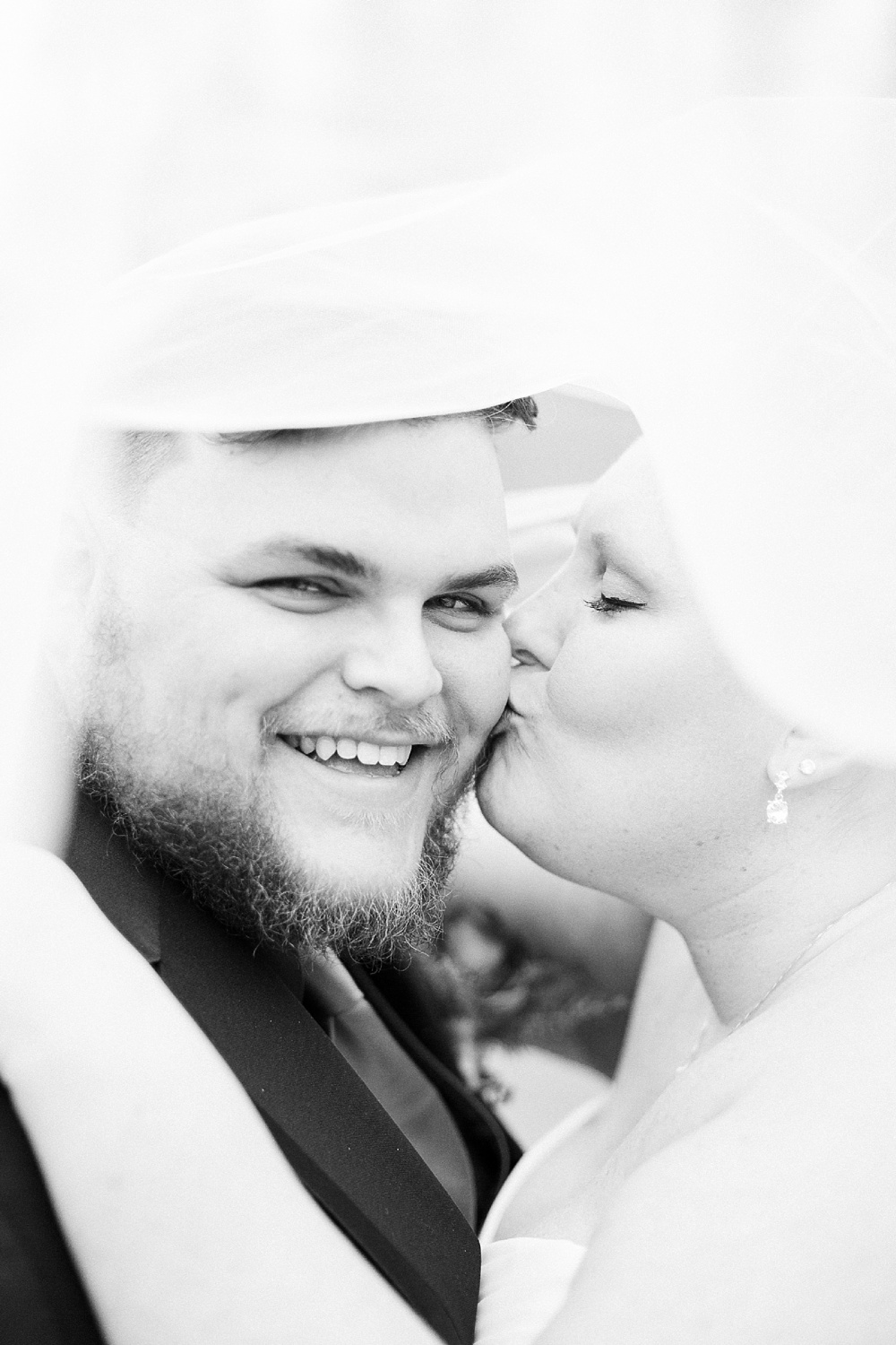 grooms smiles as bride kisses him on the cheek