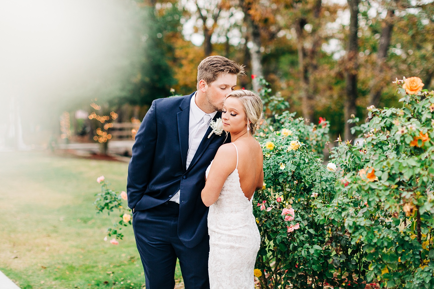 groom kisses bride on top of her head in a rose garden
