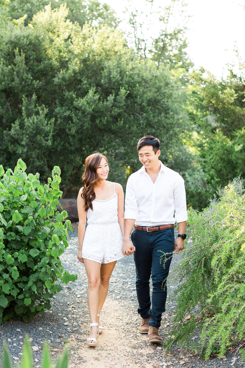 young asian couple walks and holds hands
