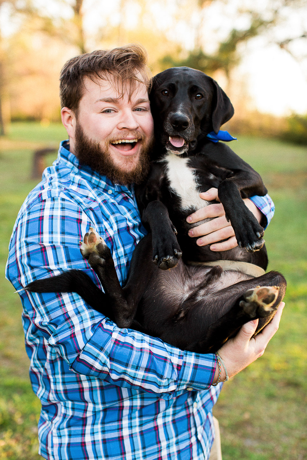Man holds dog like a baby at Goldsboro NC engagement session
