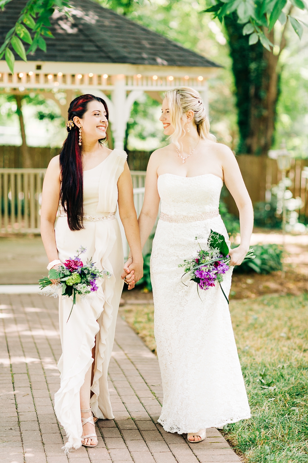 brides walking hand in hand down a brick path